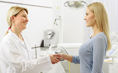 Dentist shaking hands with young woman